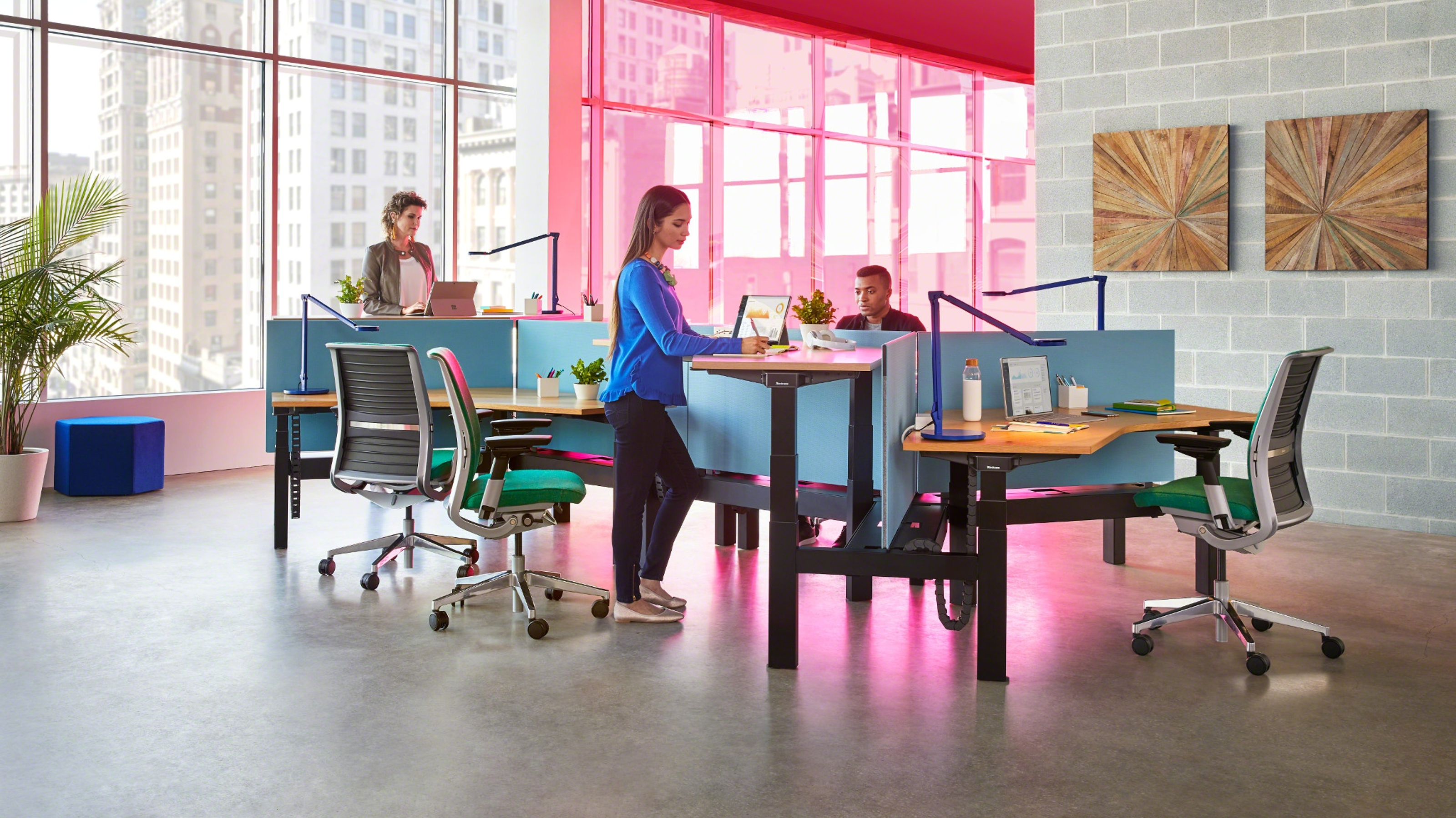 Pink lighted desking area with people talking to each other