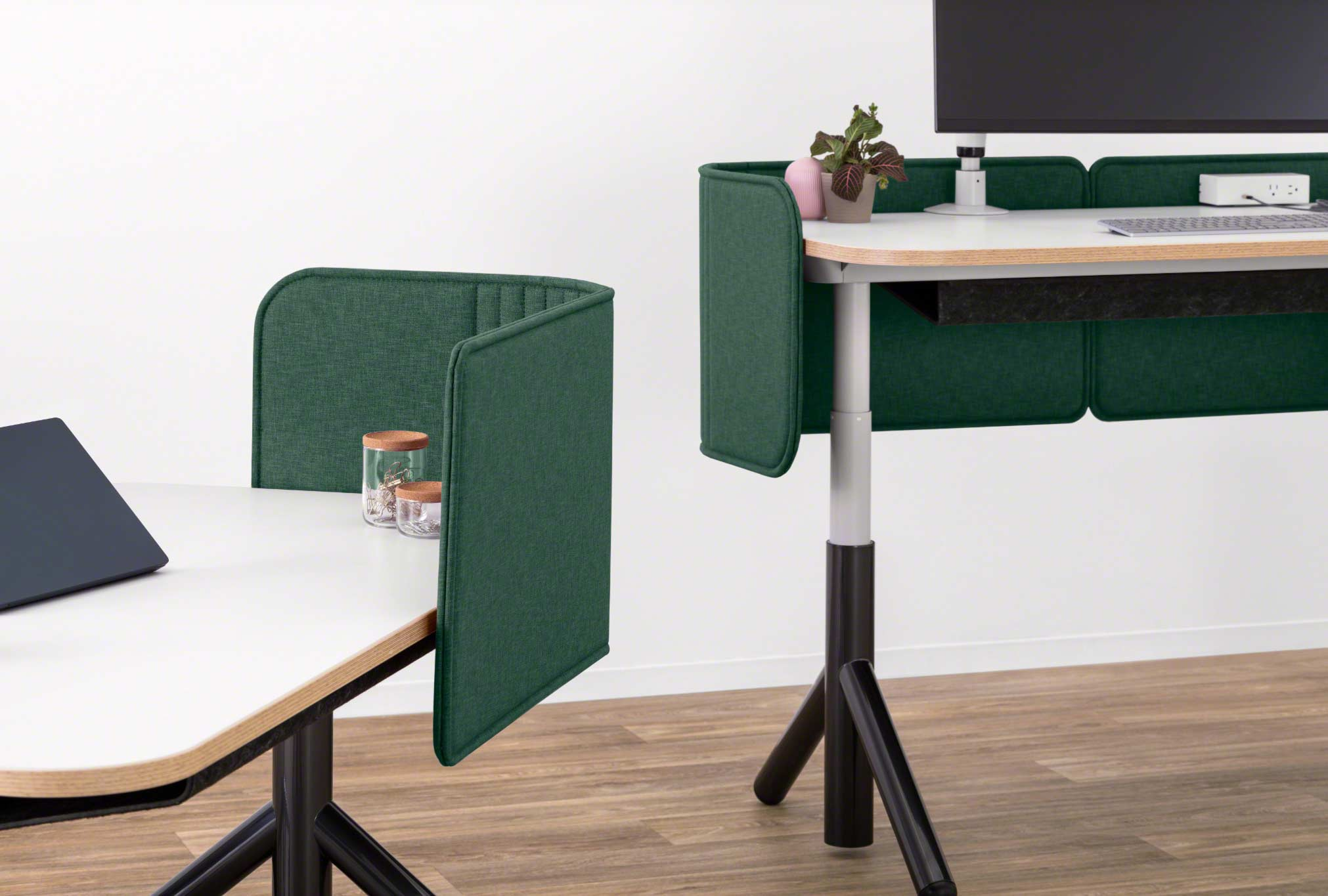 Close-up of Two Steelcase Flex height-adjustable desks pictured with green privacy screens attached.